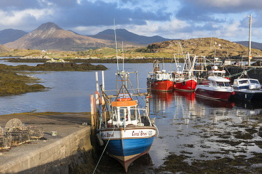 HMS3332991 Ireland, County Galway, Ballynakill, Connemara, wooden boats and fishing boats in the harbor, Tully Mountains and Twelve Bens mountains in the background