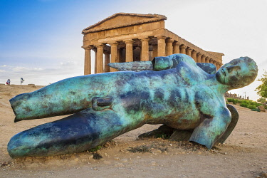 HMS3410262 Italy, Sicily, Agrigento, Valley of the Temples, UNESCO World Heritage site, temple of Concordia and bronze statue Fallen Icare by the french-polish sculptor Igor Mitoraj