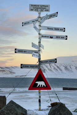 HMS3245538 Norway, Svalbard, Spitzbergen, Longyearbyen, direction and distance signs in front of Longyearbyen Airport and warning sign of potential danger of presence of polar bear