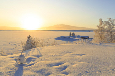 HMS3289388 Sweden, Lapland, region listed as World Heritage by UNESCO, Norrbotten County, Sunrise over a lake and a cottage