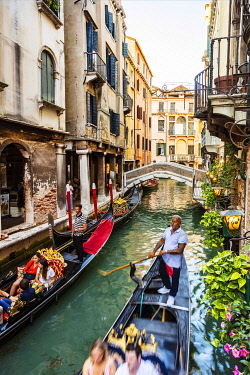 ITA14880 Italy. Veneto. Venice. Gondoliers rowing a gondola in one of the Canals of Venice in the Sestiere di San Marco.