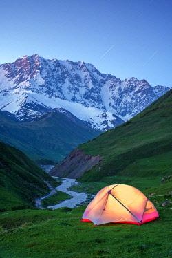 GEO0493AW Camping at the head of Enguri gorge in front of Shkhara peak, the highest point in Georgia. Ushguli, Samegrelo-Zemo Svaneti region, Georgia.
