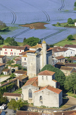 HMS3416558 France, Vendee, Bazoges en Pareds, the donjon and the church before a linen field (aerial view)