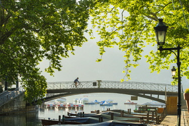HMS3429601 France, Haute Savoie, Annecy, cyclist on the bridge of the Loves at the sunrise and the beginning of the canal du Vasse