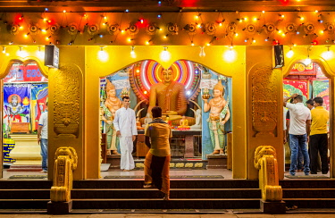 CLKMC113302 Kataragama, Monaragala District, Uva, Sri Lanka, Southern Asia. A man walks into a temple at night in Kataragama holy town