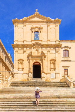 CLKGA115307 Young woman climbing the stairs of San Francesco all'Immacolata church, Noto, Siracusa province, Sicily, Italy (MR)