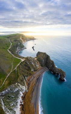 CLKMC113756 Aerial view at sunrise of the Durdle Door, a natural limestone arch on the Jurassic Coast near Lulworth in Dorset, Southern England.