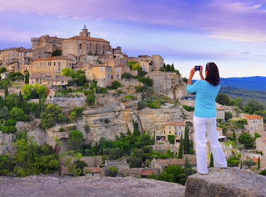 FRA11591AW France, Vaucluse, Provence, Gordes, woman standing with camera at viewpoint (MR)