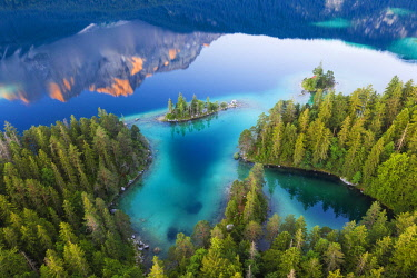 IBXMAN04970638 Eibsee lake with Braxen island and water reflection of the Zugspitze in the morning light, near Grainau, Werdenfelser Land, aerial view, Upper Bavaria, Bavaria, Germany, Europe