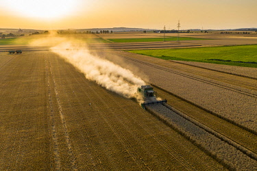 IBXMOX04954926 Aerial view, combine harvester, driving in the evening sun over a dry field with a lot of dust, Wetterau, Hesse, Germany, Europe