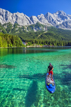 GER11906 A stand up paddler crosses the Eibsee Lake with Germany's highest mountain, the Zugspitze in the background,  Eibsee, Grainau, Bavaria, Germany.