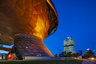 GER11913 Twilight view of the main entrance to BMW Welt (BMW World) , a multi-functional customer experience and exhibition facility of the BMW Company with the BMW Headquarters in the background in Am Riesenf...
