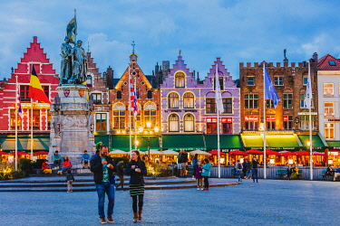 BEL1938AW Tourists walking in Market Square in Bruges by night, Belgium