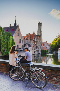 BEL1956AW A couple enjoying the view of Bruges old city reflecting in the water canal at sunset, Belgium