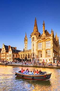BEL1957AW A water full of tourists in the canal with the Ghent buildings reflecting in the water at sunset, Belgium