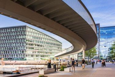 DEN0431AW Tourists walking under a bike pedestrian bridge with the Aller Media building in the background, Denmark