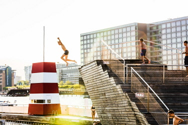 DEN0435AW Young people diving into a swimming pool  in a water canal in Copenhagen, Denmark