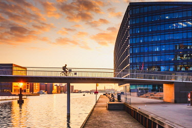 DEN0444AW A woman riding a bike on the bike bridge over the water canal, Copenhagen with the Aller Media building in the background, Denmark