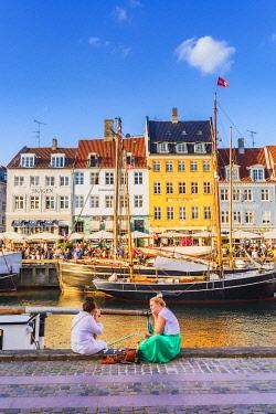 DEN0463AW A couple sitting along the water canal called Nyvan in Copenhagen, Denmark