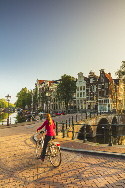 A woman riding a bike on a bridge over a canal in Amsterdam at sunset, Holland/Netherlands