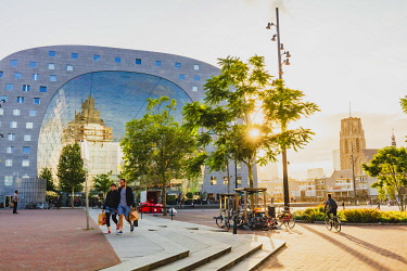 People walking in Rotterdam with the sun setting beyond the Market Hall, Holland/Netherlands