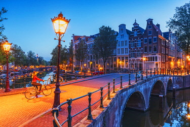 NLD1077AW A woman riding a bike by night in Amsterdam along Keizersgracht canal in Amsterdam, Holland/Netherlands
