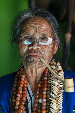 Close-up portrait of old lady with glasses and traditional facial tattoo smoking a pipe, Mindat, Mindat Township, Mindat District, Chin State, Myanmar