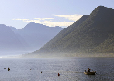 MNT0051AW Montenegro, Bay of Kotor, Perast. Man rowing towards the village on a misty morning.