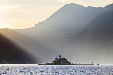 MNT0061AW Montenegro, Bay of Kotor, Perast. Shaft of light on Our Lady of the Rock Island.
