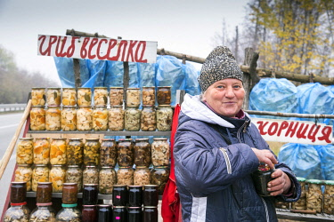 UA01159 Ukraine, Countryside, Portrait Of Farmer And Her Roadside Farm Stand, Mushrooms, Honey, Apples, And Jams