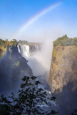 ZIM2719 Victoria Falls, Zimbabwe, Africa. Rainbow appears in the spray coming up from the gorge in front of the Victoria Falls.