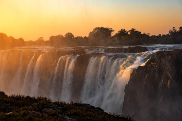 ZIM2727 Victoria Falls, Zimbabwe, Africa.  The main cataract of the Victoria Falls at sunset.