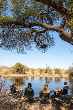 ZIM2841 Hwange National Park, Zimbabwe, Africa.  Family on safari relaxing in the shade by a waterhole