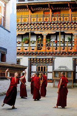 IBLDRN03578378 Group of young monks practicing a religious dance in the courtyard of Mongar Dzong fortress, Mongar, Mongar District, Bhutan, Asia