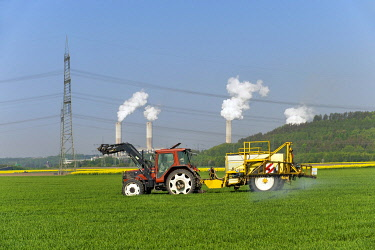 IBLFHR01900155 Tractor with trailer dispensing pesticides in a grain field, Grevenbroich, North Rhine-Westphalia, Germany, Europe