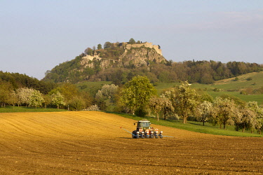 IBLMIS01902609 Ruins of Hohentwiel Fortress behind a tractor ploughing a field, Konstanz district, Baden-Wuerttemberg, Germany, Europe