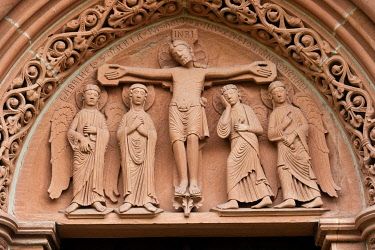 IBLRAI03568230 Relief image of Jesus on the cross over the north portal, the so-called bride's door, Romanesque Church of St. Mary, Gelnhausen, Hesse, Germany, Europe