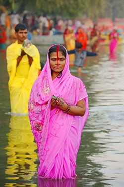 IBLCHT03683220 Man and a woman wearing a sari standing in water during the Hindu Chhath Festival, New Delhi, Delhi, India, Asia