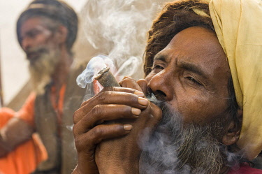 IBLFBD03152365 Udaisin Sadhu, holy man, smoking marihuana at the Sangam, the confluence of the rivers Ganges, Yamuna and Saraswati, during Kumbha Mela festival, Allahabad, Uttar Pradesh, India, Asia