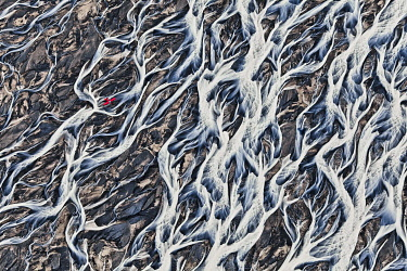 IBLMPW02201465 Aerial view, a red single-engine lightweight airplane flying over the flow structures of the melt water branching out in all directions, melt water of the Vatnajoekull glacier on the vast sand plain o...