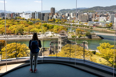 IBLMMW05035086 Woman looking from observation platform of Hiroshima Orizuru Tower, panoramic view over the city with atomic bomb dome, Atomic Bomb Dome, and Hiroshima Peace Park, Peace Monument, Hiroshima Peace Park...