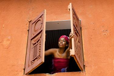 HMS3648552 Benin, Abomey, woman opening window of Abomey museum