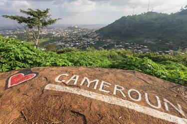 HMS3576263 Cameroon, Centre Region, Mfoundi Department, Yaounde, Mount Febe, elevated view of Yaounde north western neighbourhoods with a Love Cameroon tag in the foreground