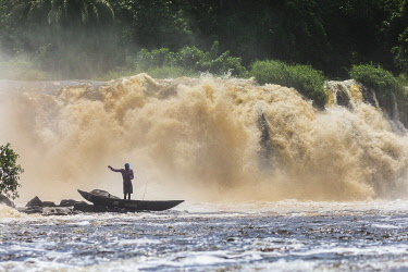 HMS3576279 Cameroon, South Region, Ocean Department, Kribi, fisherman in a canoe in front of Lobe Waterfall