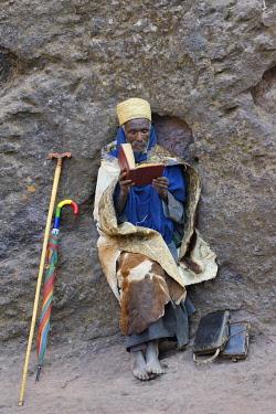 HMS3611604 Ethiopia, Lalibela, World Heritage Site, Rock-hewn church of Bieta Giyorgis (12-13th C), Hermit wrapped in cow skin reading the bible