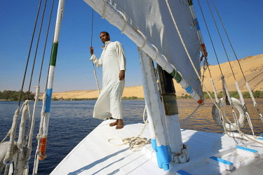 HMS3640544 Egypt, Upper Egypt, Aswan, Nubian sailor in front of his felucca all sails erected sailing on the Nile in front of a high sand dune of the left bank