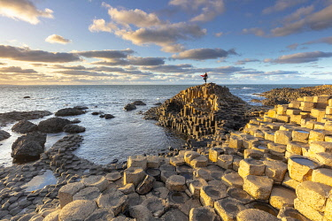 NIR8958AW Europe, United Kingdom, Northern Ireland,  County Antrim, Ulster Region, Giant's Causeway, a woman stands on the basalt rocks at the Giant's Causeway
