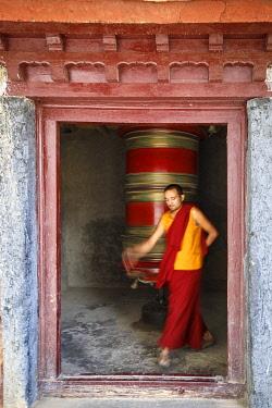 HMS3430926 India, state of Jammu and Kashmir, Himalaya, Ladakh, Gompa (monastery) of Lamayuru (3510m) of the Kagyupa order, a lama turns a big prayer wheel
