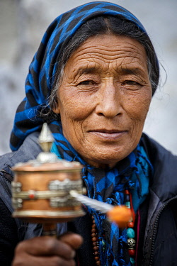 HMS3422579 India, state of Jammu and Kashmir, Himalaya, Ladakh, Zanskar, an elderly woman from Hanupatta village (3760m) turns a prayer wheel