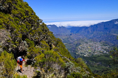 HMS3298418 France, Reunion island, Cilaos, hiker and sea of clouds in the Cilaos cirque, listed as World Heritage by UNESCO